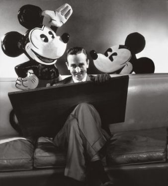 ca. October 1933, USA --- Walt Disney seated with drawing board on his lap and representations of his creations Mickey and Minnie Mouse behind. --- Image by © Condé Nast Archive/Corbis